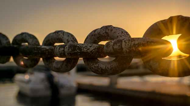 a thick chain near a dock at sunset