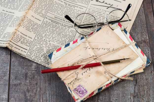 glasses, a fountain pen, and a stack of envelopes on a newspaper