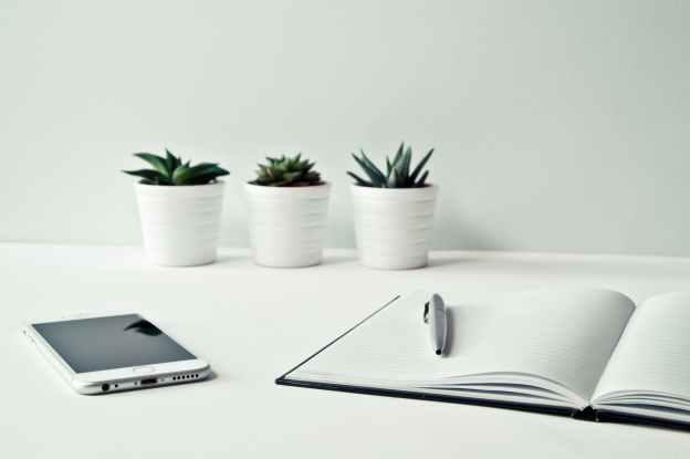 a smartphone next to an open notebook