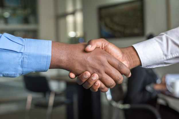 two men shaking hands in an office